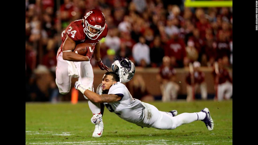 TCU safety Niko Small loses his helmet while trying to tackle Oklahoma's Rodney Anderson on Saturday, November 11. Anderson scored four touchdowns as Oklahoma won 38-20 and took sole possession of first place in the Big 12 Conference.