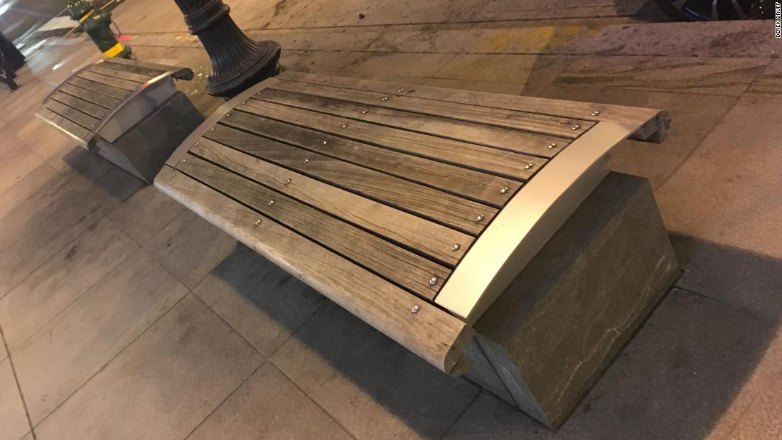 Sometimes hostile architecture is subtle. Instead of unwelcoming armrests, this wooden bench is designed with a curved base, to prevent users from lying down on it.