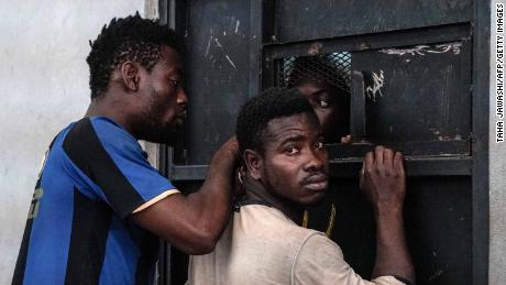 TOPSHOT - Illegal immigrants are seen at a detention centre in Zawiyah, 45 kilometres west of the Libyan capital Tripoli, on June 17, 2017. 