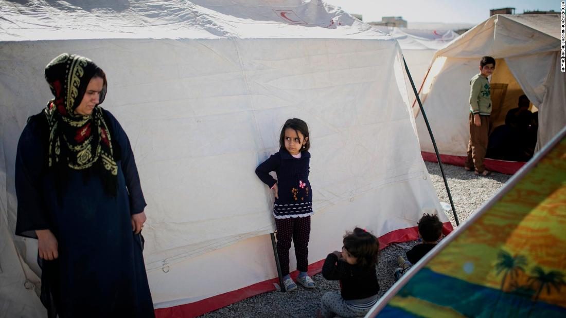 Residents stand between tents in a temporary camp erected for quake survivors in Sarpol-e Zahab.