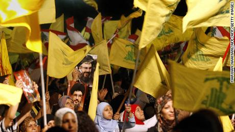 "Images of Hezbollah chief Hassan Nasrallah are seen among scores of Hezbollah and Lebanese national flags being waved by Hezbollah supporters during a ceremony to mark first anniversary of the war with Israel, 14 August 2007. Nasrallah reiterated to a mass rally broadcast live on television that his Shiite group had won a divine victory. ""Today is the anniversary of the divine victory,"" Nasrallah told the thousands of men, women and children who had gathered in an empty lot of Beirut's southern suburb of Dahiyeh controlled by Hezbollah. AFP PHOTO/MARWAN NAAMANI (Photo credit should read MARWAN NAAMANI/AFP/Getty Images)"