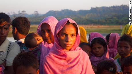 A group of Rohingya refugees, including this pregnant woman, wait on the roadside to hitchhike to nearby refugee camps.