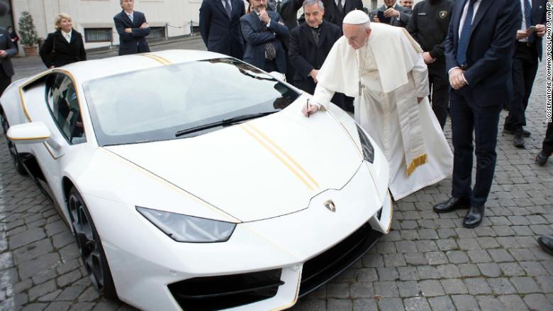 Pope Francis writes on the hood of a Lamborghini donated to him by the luxury sports car maker, at the Vatican.