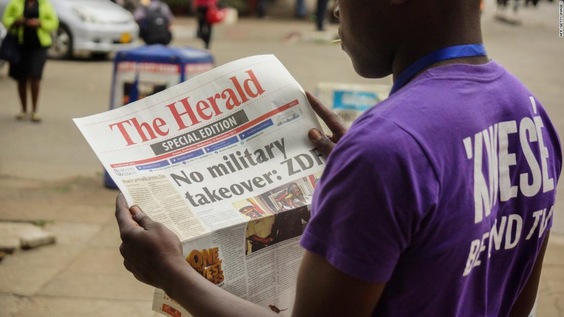A man in Harare reads the front page of a special edition of The Herald newspaper on November 15.
