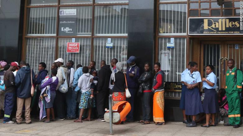 Members of the public wait outside a bank to withdraw cash in Harare on Wednesday.