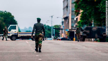 Zimbabwean soldiers stand at an intersection as they regulate traffic in Harare on November 15, 2017. 