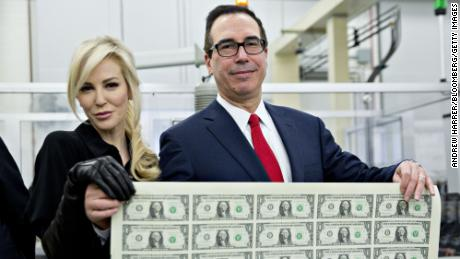 "Steven Mnuchin, U.S. Treasury secretary, right, and his wife Louise Linton hold a 2017 50 subject uncut sheet of $1 dollar notes bearing Mnuchin's name for a photograph at the U.S. Bureau of Engraving and Printing in Washington, D.C., U.S., on Wednesday, Nov. 15, 2017. A change in the Senate tax-overhaul plan that would expand a temporary income-tax break for partnerships, limited liability companies and other so-called ""pass-through"" businesses won the endorsement of a national small-business group today. Photographer: Andrew Harrer/Bloomberg via Getty Images"
