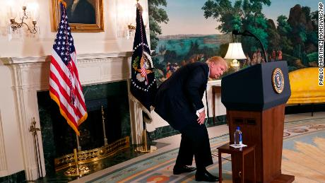 President Donald Trump looks for bottle water as he pauses while speaking about his trip to Asia in the Diplomatic Reception Room of the White House, Wednesday, Nov. 15, 2017 in Washington. (AP Photo/Pablo Martinez Monsivais)
