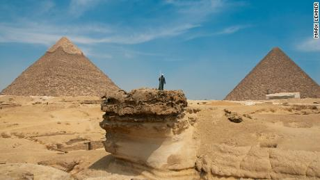 A man stands on an outcrop on the Giza plateau, surrounded by land quarried in antiquity.