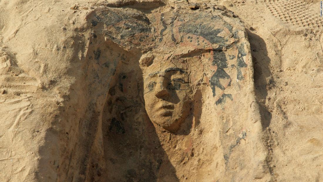 "The face mask of a slipper coffin, a form of pottery coffin, stands in relief.  The grave is dated from the Late Period and is situated south of the Wall of  the Crow, an ancient stone wall bordering the ""workers' town"" -- the so-called ""Lost City of the Pyramids."""
