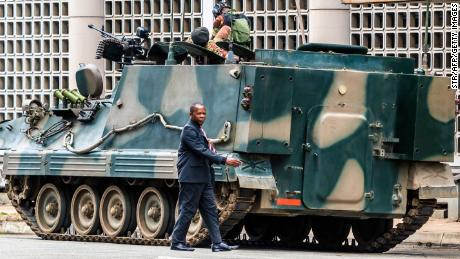 "A man walks past a military tank parked on the side of a street in the Zimbabwean capital Harare on November 16, 2017, a day after the military announced plans to arrest ""criminals"" close to the president. 