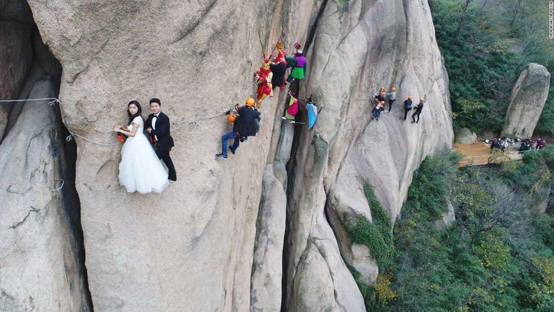 A couple takes a wedding photo while hanging off a cliff in Zhumadian, China, on Saturday, November 11.