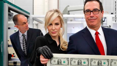 Treasury Secretary Steven Mnuchin, right, and his wife Louise Linton, hold up a sheet of new $1 bills, the first currency notes bearing his and U.S. Treasurer Jovita Carranza's signatures, Wednesday, Nov. 15, 2017, at the Bureau of Engraving and Printing (BEP) in Washington. The Mnuchin-Carranza notes, which are a new series of 2017, 50-subject $1 notes, will be sent to the Federal Reserve to issue into circulation. At left is BEP Director Leonard Olijar.