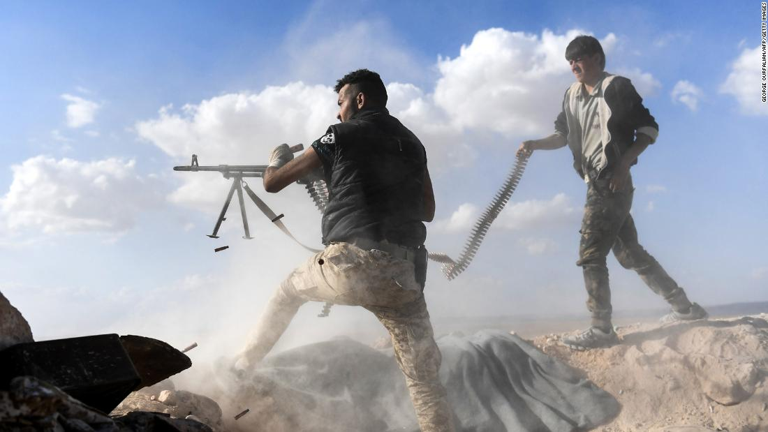A member of Syria's pro-regime forces fires a machine gun during an advance on rebel-held positions west of Aleppo on Saturday, November 11.