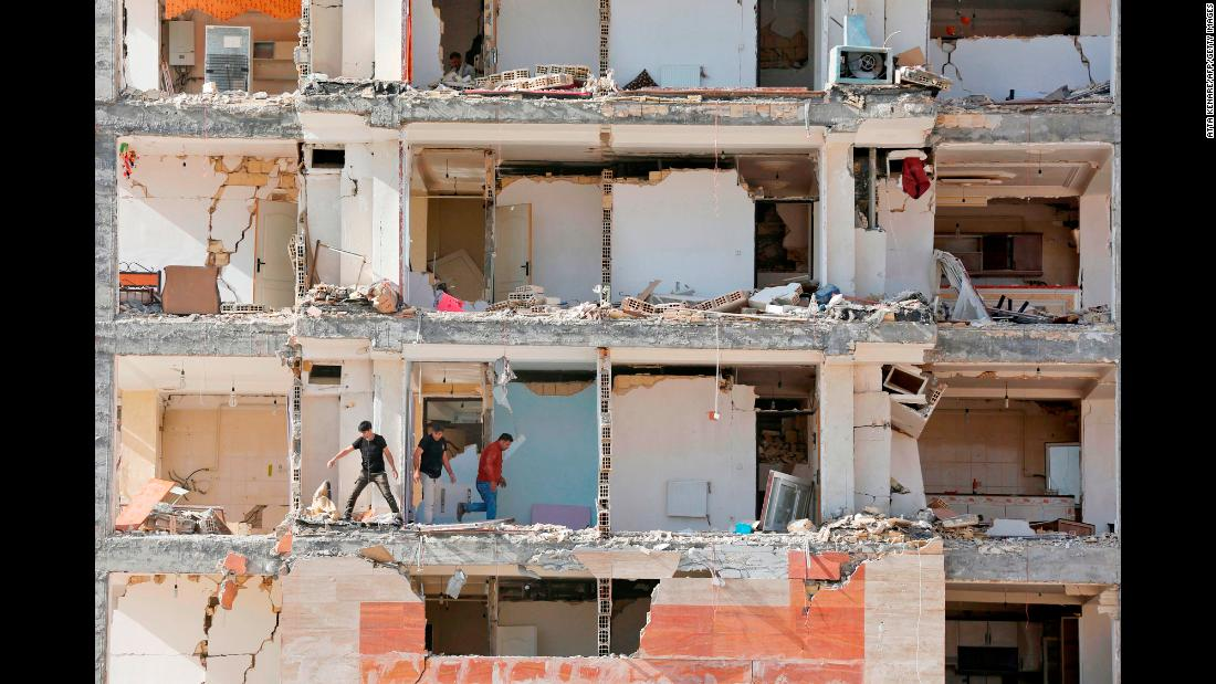 People walk in an earthquake-damaged building in Sarpol-e Zahab, Iran, on Wednesday, November 15. Hundreds of people were killed in the disaster. Thousands were left homeless.