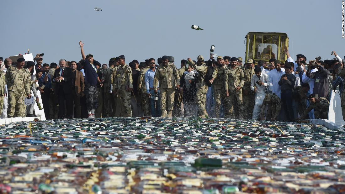 Officials with the Pakistan Coast Guards throw confiscated bottles of liquor before destroying them on the outskirts of Karachi on Monday, November 13.