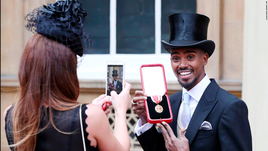 British track star Mo Farah poses for his wife, Tania, after being awarded a knighthood by Queen Elizabeth II on Tuesday, November 14. Farah, a distance runner, has won four Olympic gold medals.