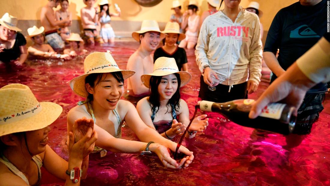 A man pours a bottle of wine on the hands of a woman bathing in a colored bath at a hot-spring resort in Hakone, Japan, on Thursday, November 16. Thursday marked the official release of the wine, a 2017 Beaujolais Nouveau.