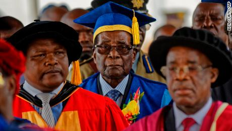 Zimbabwe's President Robert Mugabe, center, arrives to preside over a student graduation ceremony at Zimbabwe Open University on the outskirts of Harare, Zimbabwe on Friday. Mugabe is making his first public appearance since the military put him under house arrest earlier this week.