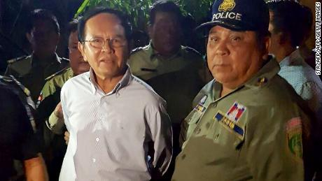 Cambodian opposition leader Kem Sokha (left) is escorted by police at his home in Phnom Penh on September 3, 2017.