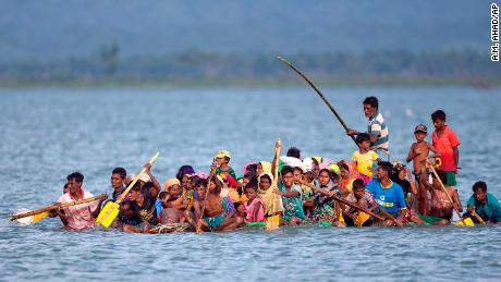 Rohingya Muslims travel on a raft made from plastic containers on the Naf river from Myanmar into Bangladesh.