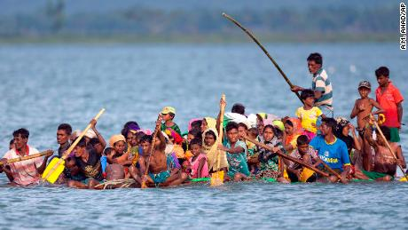 Rohingya Muslims travel on a raft made with plastic containers on which they crossing over the Naf river from Myanmar into Bangladesh, near Shah Porir Dwip, Bangladesh, Sunday, Nov. 12, 2017. (AP Photo/A.M. Ahad)