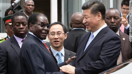 China's President Xi Jinping (2nd R) shakes  hands  with Zimbabwe's President Robert Mugabe (2nd L) as he arrive on December 1, 2015 in Harare.  China's President Xi Jinping visited Zimbabwe on December 1 on a rare trip by a world leader to a country shunned by Western powers over President Robert Mugabe's widely-criticised record on human rights. . The two leaders held talks and oversaw the signing by their ministers of 10 agreements and memorandums of understanding covering energy, aviation, telecommunications and investment promotion deals to shore up Zimbabwe's economy, which has fallen into dire straits under Mugabe's rule.  / AFP / JEKESAI NJIKIZANA        (Photo credit should read JEKESAI NJIKIZANA/AFP/Getty Images)