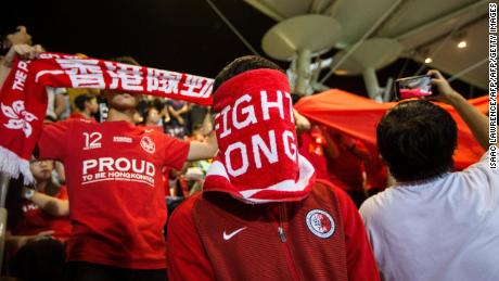 A Hong Kong fan covers his face during the Chinese national anthem before an international friendly football match between Hong Kong and Bahrain at Mong Kok Stadium in Hong Kong on November 9, 2017. Hong Kong's government on November 4 said that a law passed by China punishing anyone who disrespects the national anthem with up to three years in prison will also apply in the semi-autonomous territory, once the authorities enact a local version of the legislation and get it passed through the legislature. Hong Kong football fans have booed the anthem when it is played at matches for years, as concerns grow about the city's liberties coming under threat. / AFP PHOTO / Isaac LAWRENCE        (Photo credit should read ISAAC LAWRENCE/AFP/Getty Images)