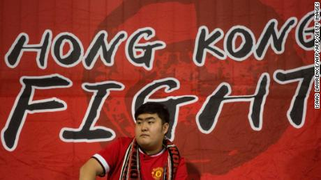 A Hong Kong fan sits in front of a flag before an international friendly football match between Hong Kong and Bahrain at Mong Kok Stadium in Hong Kong on November 9, 2017.