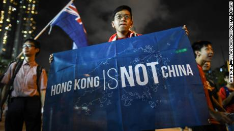 "In this October 10, 2017 photograph, a flag that reads ""Hong Kong is not China"" is displayed by a local football fan in front of the old British colonial flag after a match between Hong Kong and Malaysia in Hong Kong."