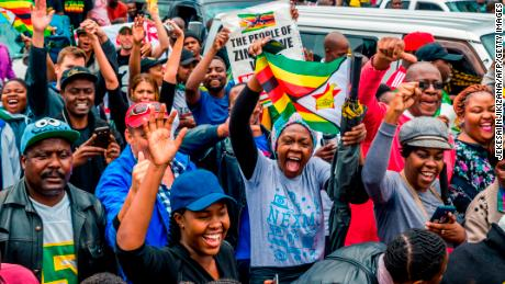 People shout slogans and wave Zimbabwean national flags during a demonstration demanding the resignation of Zimbabwe's president on November 18, 2017 in Harare.  Zimbabwe was set for more political turmoil November 18 with protests planned as veterans of the independence war, activists and ruling party leaders called publicly for Zimbabwe's President to be forced from office. / AFP PHOTO / Jekesai NJIKIZANA        (Photo credit should read JEKESAI NJIKIZANA/AFP/Getty Images)