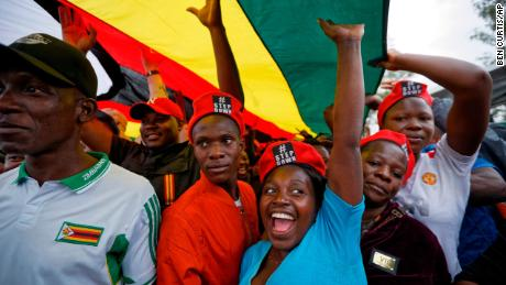 Protesters raise their fists under a large national flag, at a demonstration of tens of thousands at Zimbabwe Grounds in Harare, Zimbabwe Saturday, Nov. 18, 2017. Opponents of Mugabe are demonstrating for the ouster of the 93-year-old leader who is virtually powerless and deserted by most of his allies. (AP Photo/Ben Curtis)
