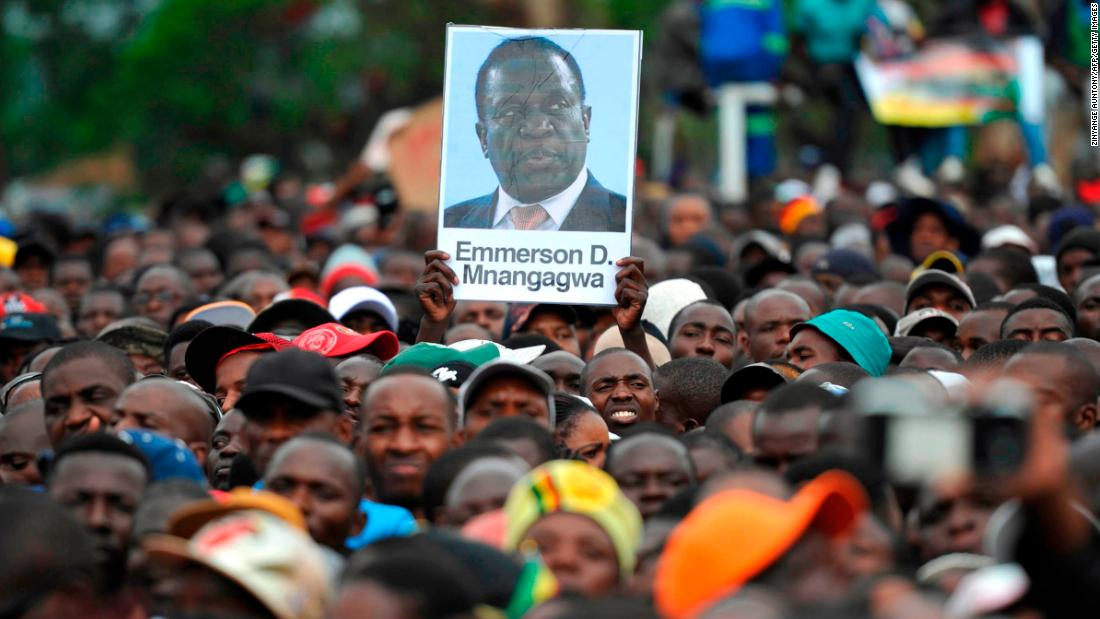 People hold a portrait of Zimbabwe's former vice president, Emmerson Mnangagwa, during a demonstration demanding Mugabe's resignation on November 18. ZANU-PF announced Mnangagwa as its new party leader. He was fired by Mugabe on November 6.