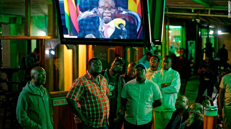 Zimbabweans watch Mugabe's televised address to the nation at a bar in downtown Harare Sunday.