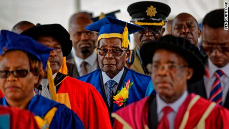 Mugabe, center, presides over a student graduation ceremony at Zimbabwe Open University on Friday.