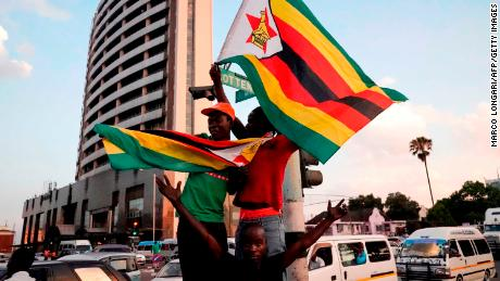 People holding Zimbabwean flags celebrate in the street after the resignation of Zimbabwe's president on November 21, 2017 in Harare.
