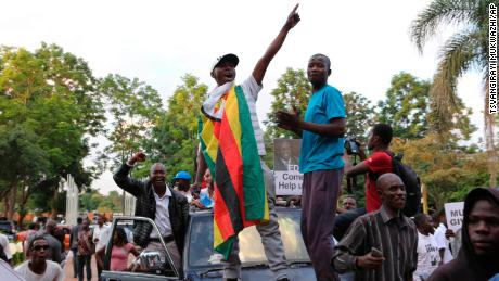 Zimbabweans raise their fists at the news of Robert Mugabe's resignation.