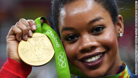 RIO DE JANEIRO, BRAZIL - AUGUST 09:  Gabrielle Douglas of the United States poses for photographs with her gold medal after the medal ceremony for the Artistic Gymnastics Women's Team on Day 4 of the Rio 2016 Olympic Games at the Rio Olympic Arena on August 9, 2016 in Rio de Janeiro, Brazil.  (Photo by Laurence Griffiths/Getty Images)