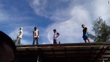 Residents of the Manus island refugee camp stand on the roof of a structure in the now-shuttered facility.