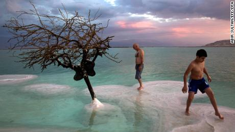epaselect epa06344355 People look at a tree covered with salt rising from a salt formation, in the middle of the Dead Sea, at the southern areas near Ein Bokek, Israel, 22 November 2017.  EPA-EFE/ABIR SULTAN