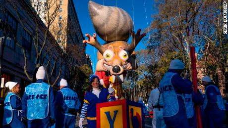Participants stand below a parade balloon before the Macy's Thanksgiving Day Parade begins in New York, Thursday, Nov. 23, 2017. (AP Photo/Craig Ruttle)