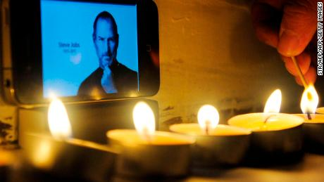 This picture taken on October 6, 2011 shows a Chinese man lighting candles to pay tribute to Steve Jobs outside an Apple store in Beijing. The death of Apple visionary Steve Jobs has left huge shoes to fill, with successor Tim Cook inheriting a company with fabulous products but also facing unrelenting assault from agile competitors.  CHINA OUT      AFP PHOTO        (Photo credit should read STR/AFP/Getty Images)