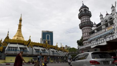 A Buddhist monk (L) crosses a street intersection fronting Sule pagoda (L) and the Bengali Sunni Jameh mosque (R) in Yangon on June 10, 2016.  While Myanmar's Muslim minority in Yangon freely marks the first Friday prayers on June 10, during Islam's holy fasting month of Ramadan, the persecuted Muslim minority Rohingya in the western state of Rakhine languish in displacement camps following bloody sectarian violence in 2012 between the Rohingya and Buddhist population. Across the Muslim world, the faithful fast from dawn to dusk and strive to be more pious during the holy month, which ends with the Eid holiday. / AFP / ROMEO GACAD        (Photo credit should read ROMEO GACAD/AFP/Getty Images)