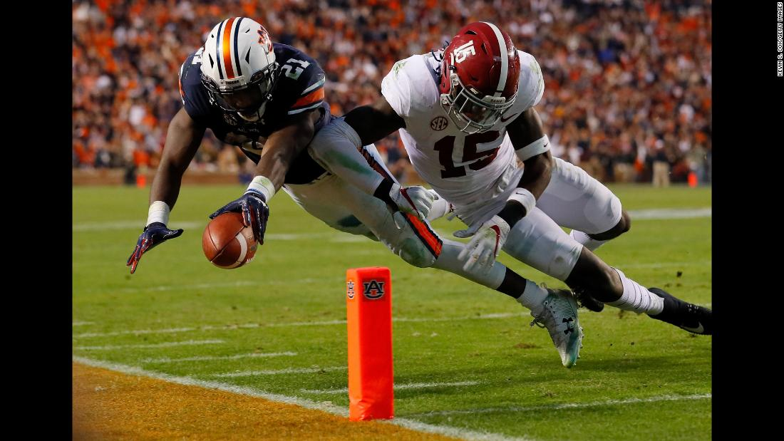 Auburn running back Kerryon Johnson, left, is hit by Alabama's Ronnie Harrison while diving for the goal line on Saturday, November 25. Auburn knocked off its top-ranked rival 26-14 to win the SEC West Division and clinch a spot in the conference title game.
