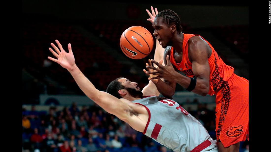 Stanford's Josh Sharma, left, draws a charge on Florida's Deaundre Ballard during a college basketball game in Portland, Oregon, on Thursday, November 23.