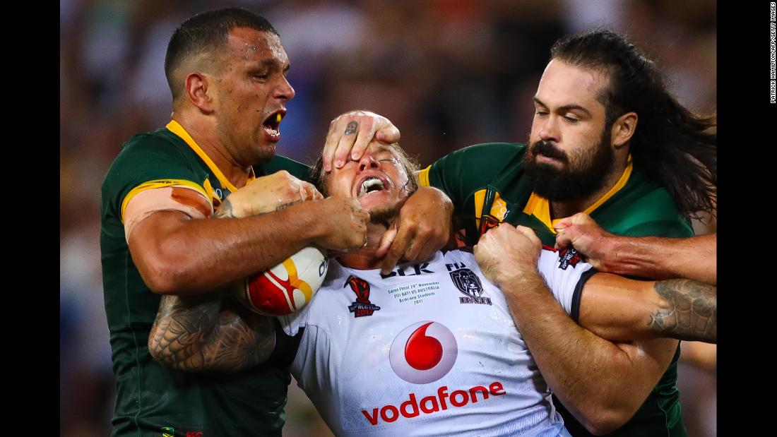 Fiji's Ashton Sims is tackled by Australia's Will Chambers, left, and Aaron Woods during the semifinals of the Rugby League World Cup on Friday, November 24. Australia won 54-6 to advance to the final against England.