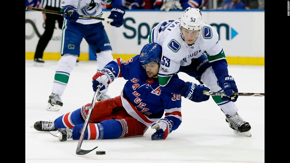 New York Rangers forward Mats Zuccarello tries to corral the puck near Vancouver's Bo Horvat during an NHL game in New York on Sunday, November 26.