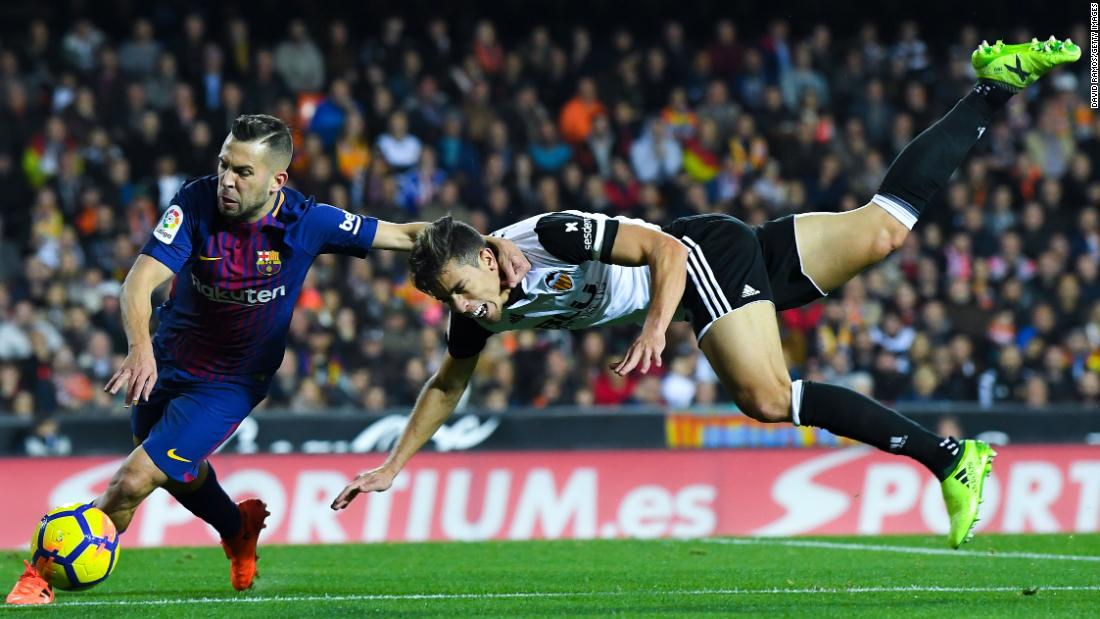 Barcelona's Jordi Alba, left, dribbles by Valencia's Gabriel Paulista during a Spanish league match in Valencia on Sunday, November 26.