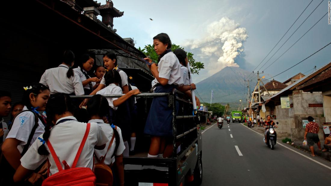Students stand on a truck on their way to go to school, with erupting Mount Agung in the distance. The National Agency for Disaster Management issued a Level 4 alert on Monday, November 27, indicating the potential for another larger eruption and recommending no public activities within 8 to 10 kilometers from the peak of the volcano.