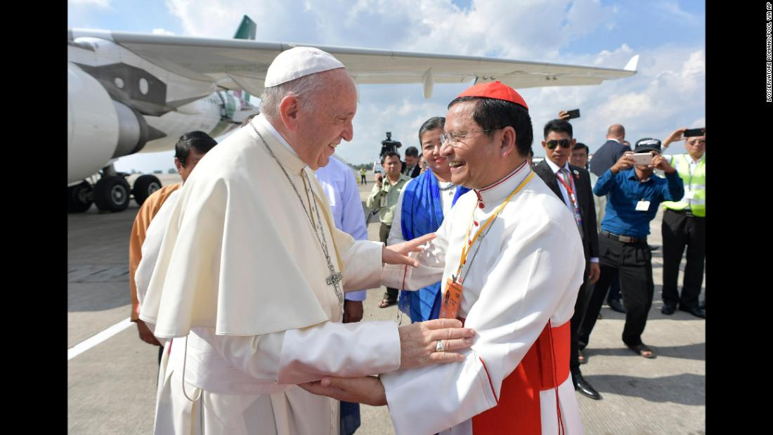 Pope Francis is received on the tarmac by Cardinal Charles Maung Bo, the archbishop of Naypyidaw.